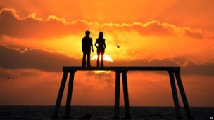 """The sun rises over the giant sculpture of a man and woman situated 300 yards out to sea off the coast of Northumberland at Newbiggin-by-the-Sea. Comprising of two 5 metre tall bronze figures of a man and a woman the sculpture is called """"the couple"""" and is by artist Sean Henry."""