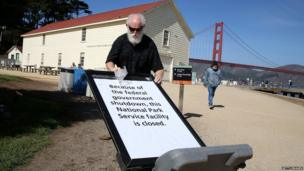 National Park Service worker Michael Faw posts a sign announcing the closure of a Park Service facility at Crissy Field