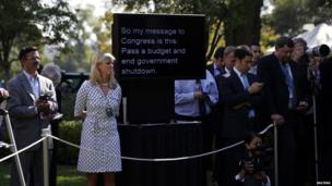 A teleprompter used by U.S. President Barack Obama to deliver remarks on the implementation of the Affordable Care Act is shown among White House staff and journalists is seen in the Rose Garden of the White House in Washington, October 1, 2013. The U.S. government began a partial shutdown on Tuesday for the first time in 17 years, potentially putting up to 1 million workers on unpaid leave, closing national parks and stalling medical research projects.