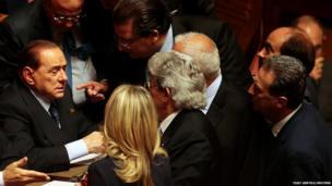 Italian centre-right leader Silvio Berlusconi (left) talks with senators