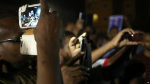 Protesters film a demonstration with their phones in Khartoum, Sudan - Sunday 29 September 2013