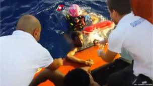 Grab from video released by the Guardia Costiera shows guards helping an immigrants out of the sea near Lampedusa (3 October 2013)