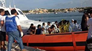 An Italian Coast Guard boat carries rescued migrants as they arrive in the port of Lampedusa on 3 October 2013.