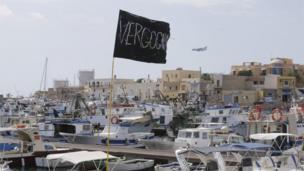 Black flag with 'Vergogna' (disgrace) flying in harbour of Lampedusa (4 Oct 2013)