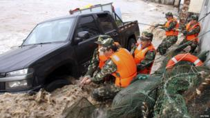 Paramilitary policemen pull up a vehicle overturned by a storm surge near the coastline, under the influence of Typhoon Fitow in Yuhuan, Zhejiang province, 6 October 2013