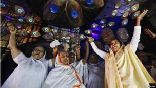 Widows sing and dance inside a marquee where an idol of Hindu goddess Durga is installed ahead of the Durga Puja festival in Kolkata (7 October 2013)