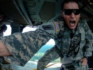US Army Captain John Litty signals for the photographer to jump out of a UH-60 Black Hawk helicopter