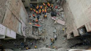 Indian rescue workers remove debris after a three-story building collapsed in New Delhi