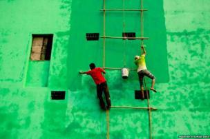 Men paint a wall