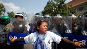 A woman reacts as police officers block the march along a street on the occasion of World Habitat Day in central Phnom Penh