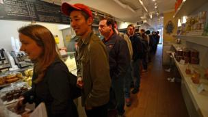 "People cue up to get a ""cronut"" at the bakery in New York where they were invented."