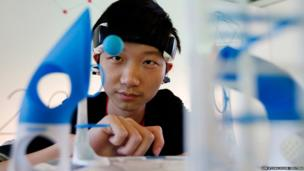 A man steers a ball through an obstacle course at the International Design Exhibition in Beijing while using his brainwaves to control the power of a fan at the bottom of the machine