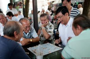 A group playing Xiangqi, sometimes called Chinese chess, in Chinatown where you will find groups playing every day.