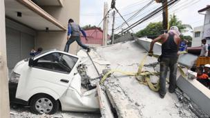 Workers use a crane to lift up concrete block that fell on a car after buildings collapsed during an earthquake