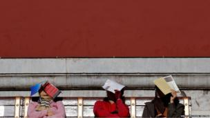 Women shade themselves from sunlight during a tour of the Forbidden City in Beijing
