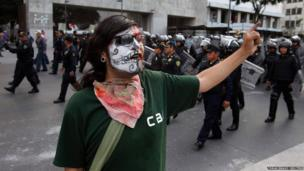 A demonstrator, with half of his face painted as a skull, yells slogans as riot policemen block a street to impede a march toward the Zocalo square in Mexico City