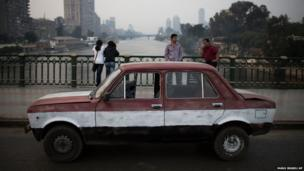 A car painted in Egypt's national flag colours is parked on a bridge over the Nile