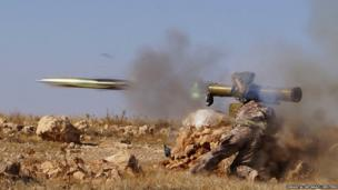 A Free Syrian Army (FSA) fighter fires an anti-tank missile