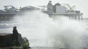 Large waves break against barriers on the seafront in Brighton