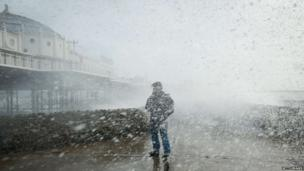 A man is soaked as large waves crash against the walls of Brighton seafront, in southern England