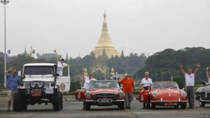 Classic cars line up for a photo with Shwedagon Pagoda in the background