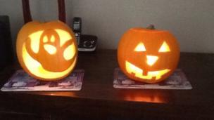 Two pumpkins, one carved with a ghost, the other with a creepy face