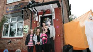 A family standing outside their home decorated for Halloween with ghosts and spiders.