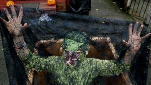 A man dressed in a swamp man costume under a net looking scary