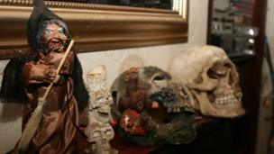 A witch and some skulls on a mantlepiece
