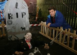 Ricky stands next to a grave with a dead person in it