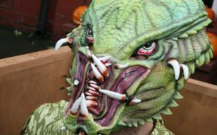 A close up of a man dressed in a green monster costume