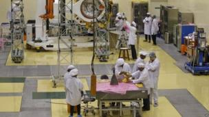 Indian engineers work with their staff next to a pyramid shaped rocket or Liquid Apogee Motor, foreground, to be installed on the Mars orbiter spacecraft, background, at the satellite centre of Indian Space Research Organization (ISRO) in Bangalore