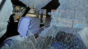 A Chinese police officer is framed by the glass window of a vehicle damaged by explosions outside the provincial headquarters of China's ruling Communist Party in Taiyuan