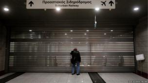 A commuter stands in front of the closed entrance to a railway station during a strike in Athens