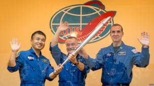 Three astronauts hold the torch for the Sochi Winter Olympics