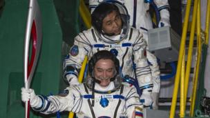International Space Station (ISS) crew members, Japanese astronaut Koichi Wakata (top) and Russian cosmonaut Mikhail Tyurin, board the Soyuz TMA-11M spacecraft with the torch of the 2014 Sochi Winter Olympic Games at the Baikonur cosmodrome.