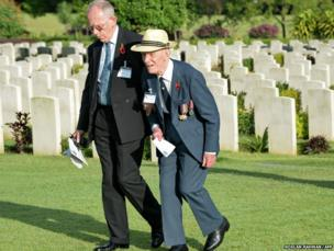 Former British World War Two prisoner-of-war James Crossan (right), assisted by his son Robin Crossan, walks past headstones to attend a remembrance service at Kranji Commonwealth Cemetery in Singapore.