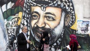 Palestinians walk past a mural of late Palestinian leader Yasser Arafat in Gaza City
