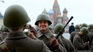 A Russian soldier dressed in Red Army World War II uniform poses for a photo while preparing to parade in Red Square