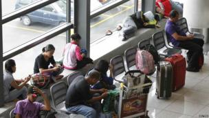 Stranded passengers wait at the lobby of Ninoy Aquino International airport in Pasay city, metro Manila, 8 November 2013