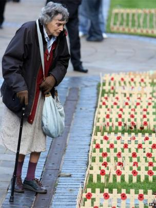 A woman looks at tributes during the Armistice Day service, at the cenotaph at City Hall, Belfast