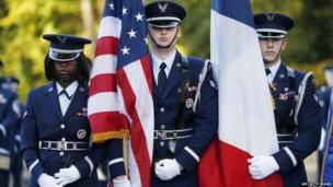 US Air Force soldiers hold French and US flags as they attend the Remembrance Day ceremony at The Lafayette Escadrille Memorial of Marnes-la-Coquette, east of Paris,