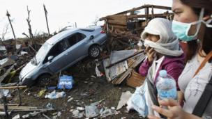 People covering their faces pass a car in debris after super typhoon Haiyan battered Tacloban City, in central Philippines, 13 November 2013