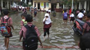 A student drinks a packet of milk as she wades through flood waters in Lopang Domba Elementary School
