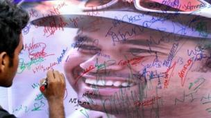 A fan of Sachin Tendulkar writes a message on a poster displayed in Bangalore on 13 November 2013