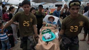 A typhoon victim is moved on a stretcher by Philippine army soldiers, at Tacloban airport on 14 November 2013