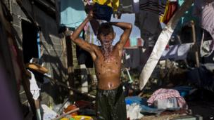 A Typhoon Haiyan survivor bathes in the ruins of his home in Guiuan, Philippines, 15 November 2013