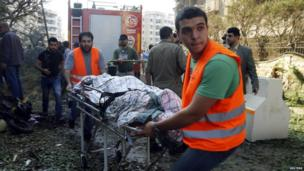 Medics transport a body at the site of explosions near the Iranian embassy in Beirut, 19 Nov