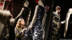 Curator Shonagh Marshall makes final touches to a dress on show in London