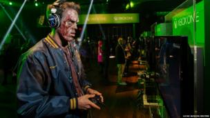 A man dressed as a zombie plays video games on an Xbox One console during a midnight launch event in New York.